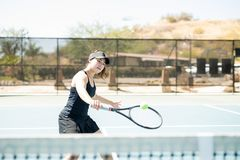 Practicing one handed backhand. Professional hispanic female tennis player hitting a backhand shot with one hand on court outdoors Royalty Free Stock Image