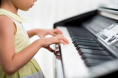 Practicing piano. Cropped image of little girl practicing piano Stock Image