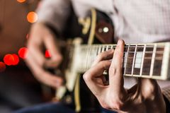 Practicing in playing guitar. Handsome young men playing guitar Royalty Free Stock Photos