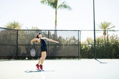 Practicing a power serve. Professional female tennis player tossing the ball and about to server the ball on court Stock Image