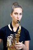 Practicing saxophone. Teenager girl practicing the saxophone stock photo