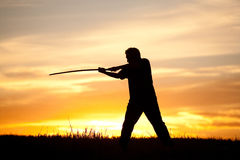 Practicing the sword at sunset. Royalty Free Stock Photo