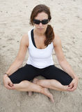 Practicing yoga. A beautiful and young woman practices yoga at a beach Stock Photos