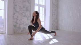 Practicing yoga. Beautiful teenage girl in sports clothing training yoga position in health club stock footage