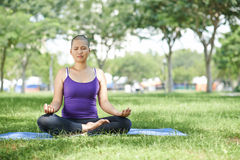 Practicing yoga. Female cancer survivor practicing yoga in the park Stock Photography