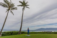 Practicing Yoga on the Maui Coast. A woman practicing yoga along the scenic coast of Maui Hawaii Stock Photography