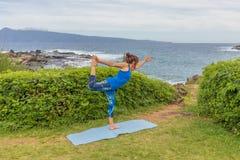 Practicing Yoga on the Maui Coast. A woman practicing yoga along the scenic coast of Maui Hawaii Stock Photos