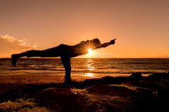 Practicing Yoga at Sunset Stock Photo