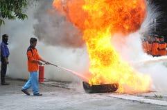 Practique el apagar del fuego con la luz de los extintores Imagen de archivo libre de regalías