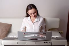 Practique el jugar del sintetizador, retrato frontal de una mujer en un piano electrónico Imagen de archivo libre de regalías