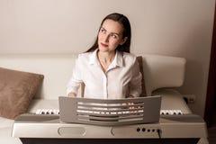 Practique el jugar del sintetizador, retrato frontal de una mujer en un piano electrónico fotografía de archivo libre de regalías