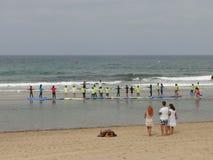 Practique surf la escuela con los niños y los profesores en la playa fotos de archivo