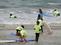 Practique surf la escuela con los niños y los profesores en la playa imagenes de archivo