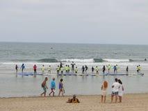 Practique surf la escuela con los niños y los profesores en la playa imagen de archivo