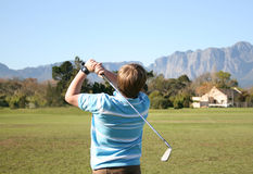 Practise. Young boy practicing golf on the driving range Royalty Free Stock Photos