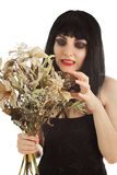 Practise witchcraft. Witch with bunch of dry flowers looking crafty isolated on white Royalty Free Stock Photos