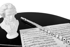 Practising the Flute (Black and White). A flute, musical score and bust of Beethoven rest on a black piano top, isolated against a white background. Black and Stock Photos