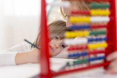 Practising math with abacus. Mother and daughter studying math through fun, learning summation and subtraction with abacus stock photography