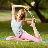 Practising pigeon pose in the park Stock Photos
