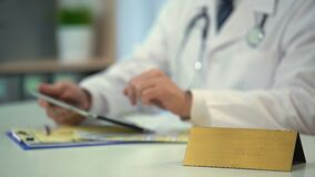 Practitioner checking clinical records on tablet, blank nameplate on table. Stock footage stock video footage