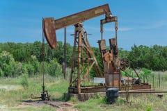 Pracująca pompowa dźwigarka pompuje ropę naftową przy odwiert naftowy miejscem w rurze obraz royalty free
