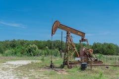 Pracująca pompowa dźwigarka pompuje ropę naftową przy odwiert naftowy miejscem w rurze zdjęcie royalty free