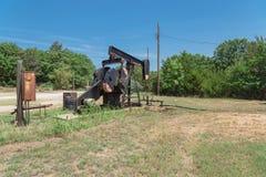 Pracująca pompowa dźwigarka pompuje ropę naftową przy odwiert naftowy miejscem w rurze fotografia stock