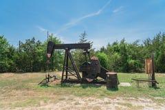 Pracująca pompowa dźwigarka pompuje ropę naftową przy odwiert naftowy miejscem w rurze fotografia royalty free