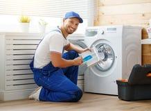 Pracującego mężczyzna hydraulik naprawia pralkę w pralni zdjęcia stock