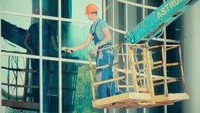 Pracującego mężczyzny szklany czysty na hydraulicznego dźwignięcia obmyć okno w wysokim biura centrum drapacz chmur budynku zbiory wideo