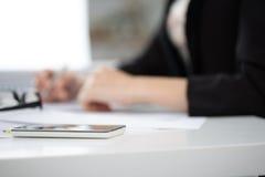 Pracującego miejsca widok Ostrość na telefonie komórkowym z biznesową kobietą Fotografia Stock