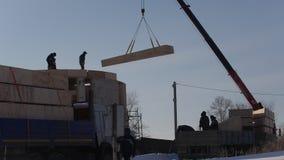 Pracujący budowa żuraw podnosi słomianego drewnianego blok dla okrąg ekologii domu zbiory