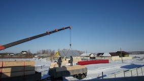 Pracujący budowa żuraw podnosi słomianego drewnianego blok dla okrąg ekologii domu zdjęcie wideo