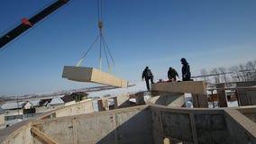 Pracujący budowa żuraw podnosi up drewnianego słoma blok - zimy budowa zbiory wideo