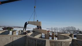 Pracujący dźwigowy huk zimy budowa - budowy intymna chałupa z drewnianym słoma blokiem - zbiory