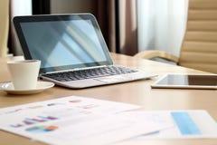 Pracujący miejsce z laptopem, cyfrowa pastylka; wykresy przy biurem obrazy stock