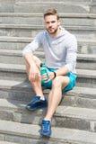 Pracujący na schodkach out Mężczyzna sportowy pojawienie trzyma bidon Mężczyzna atlety sporta odzieżowy odświeżenie Sport i Zdjęcie Stock
