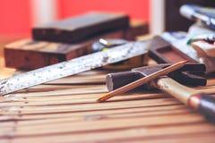 Pracujący narzędzia, młot i machinist, obciosują na drewnianym mieszkanie nieatutowy dla budowy wytłacza wzory pojęcie obrazy royalty free