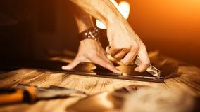 Pracujący proces rzemienny pasek w rzemiennym warsztacie Mężczyzna mienia narzędzie Garbarz w starej garbarni tabela drewna Fotografia Stock
