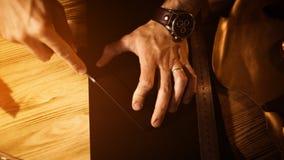 Pracujący proces rzemienny pasek w rzemiennym warsztacie Mężczyzna mienia narzędzie Garbarz w starej garbarni tabela drewna Fotografia Royalty Free