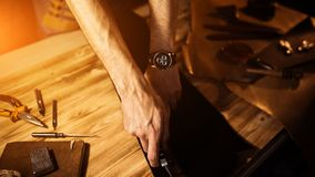 Pracujący proces rzemienny pasek w rzemiennym warsztacie Mężczyzna mienia narzędzie Garbarz w starej garbarni tabela drewna Obrazy Stock