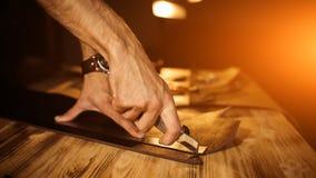 Pracujący proces rzemienny pasek w rzemiennym warsztacie Mężczyzna mienia narzędzie Garbarz w starej garbarni tabela drewna Zdjęcie Royalty Free