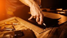 Pracujący proces rzemienny pasek w rzemiennym warsztacie Mężczyzna mienia narzędzie Garbarz w starej garbarni tabela drewna Obrazy Royalty Free
