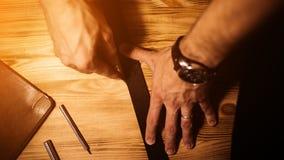Pracujący proces rzemienny pasek w rzemiennym warsztacie Mężczyzna mienia narzędzie Garbarz w starej garbarni tabela drewna Zdjęcie Stock