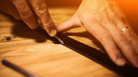 Pracujący proces rzemienny pasek w rzemiennym warsztacie Mężczyzna mienia narzędzie Garbarz w starej garbarni tabela drewna Zdjęcia Royalty Free
