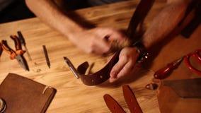 Pracujący proces rzemienny pasek w rzemiennym warsztacie Mężczyzna mienie wykonuje ręcznie narzędzie i działanie Garbarz w starym zbiory wideo