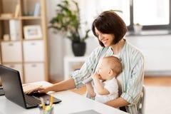 Pracuj?ca matka z ch?opiec i laptopem w domu fotografia stock