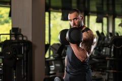 Pracujący bicepsy Z Dumbbells Out Obraz Stock