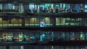 Pracuj?cy wiecz?r w szklanym budynku biurowym z mnogimi biurami z szklanych ?cian i okno timelapse zbiory