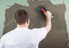 Pracujący budowniczy stosuje kleidło na ścianie dla ceramicznej płytki f Fotografia Royalty Free